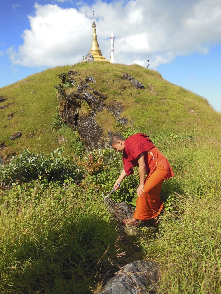 Monk geologist helping collect samples.