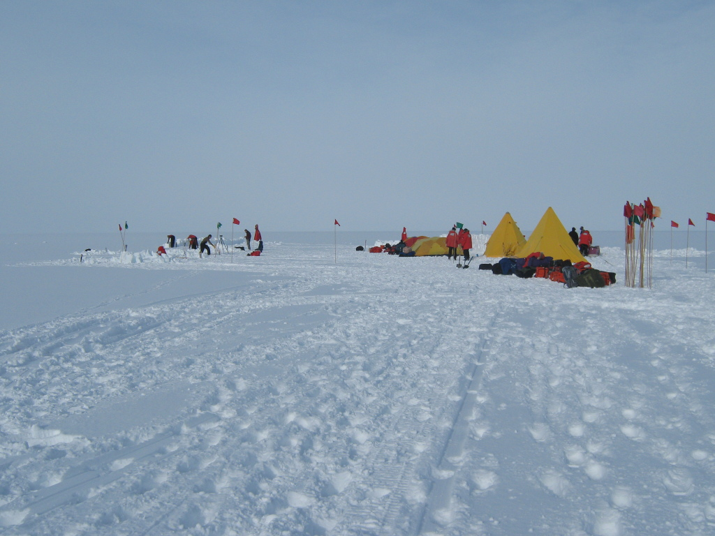 "Figure 4. Several participants at the ""Happy Camper"" campsite dig snow trenches, while others set up tents. Red and green flags mark safe routes in case of poor-visibility conditions."