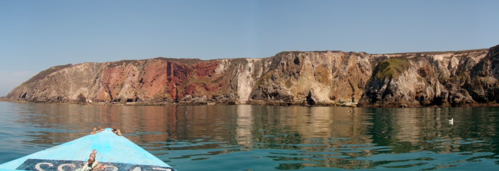 View of Cligga Head from a boat. The granite outcrops to the north (left), with the sheeted Sn-W and polymetallic sulphide veins towards the centre (red) and the country rock and elvans to the south (right).