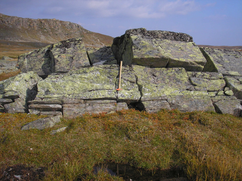 Fig. 2: Synkinematically intruded and deformed pegmatite vein in mylonitic high pressure garnet-micaschists of the continental Upper Seve nappe. Steep slope to the left is formed by massive and detrital serpentinites of the hangingwall oceanic Lower Köli nappe. Picture was taken close to the top of a 434-429 Ma extrusion wedge that exhumed high-pressure Seve nappes from mantle depths to mid-crustal levels.