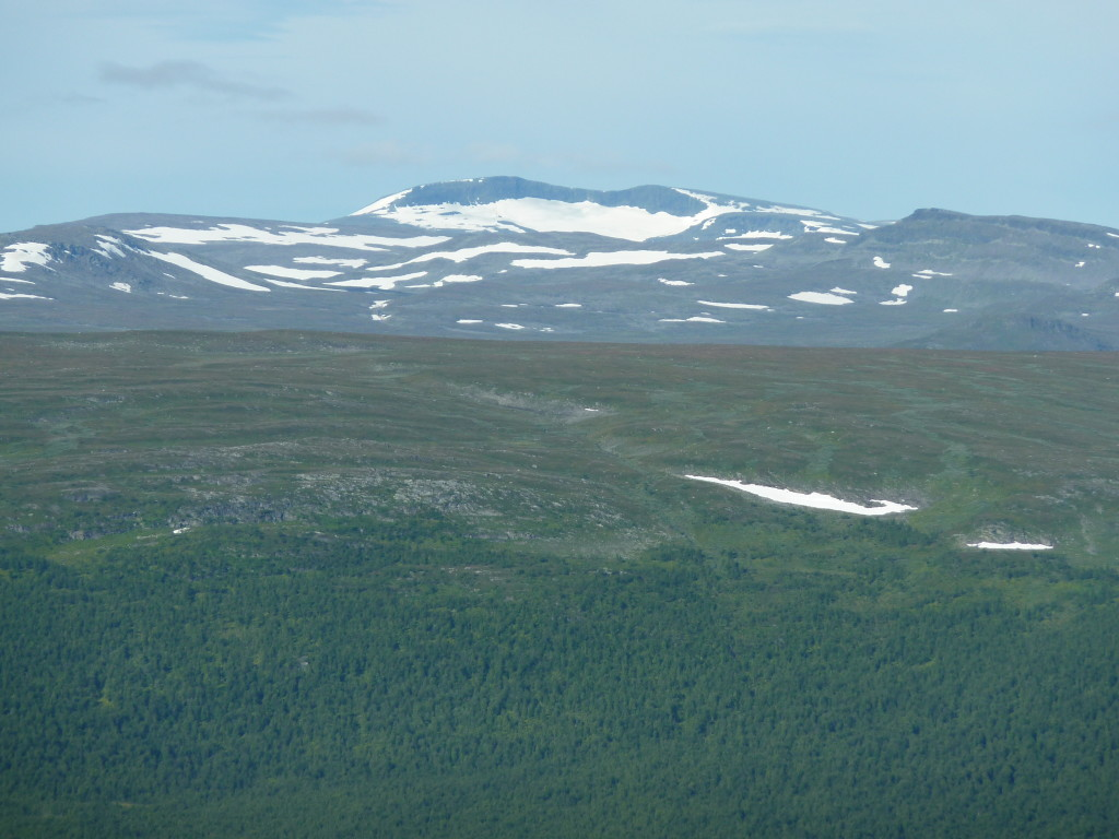 Fig. 4: View to west onto the Ammarfjället, essentially constituted by rocks of the Seve Nappe Complex, with the remote, 1611 m high Rerrogaisse mountain massiv and its characteristic relic kettle glacier. The foreground shows the western flank of the Vindelälven valley exposing metagreywackes of the Ammarnäs Nappe Complex.