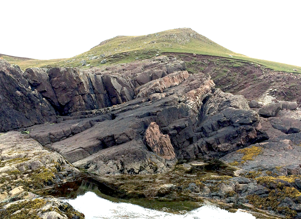 Fig. 3 – The Stac Fada Member fills most of this photo, including the ~5 metre tall subvertical faces to the left. The paler brown rocks are layers of pre-existing sandstone that were disrupted and folded by the fast-moving ejecta blanket. The nose of one of these folds is clearly visible in the centre of the photograph.