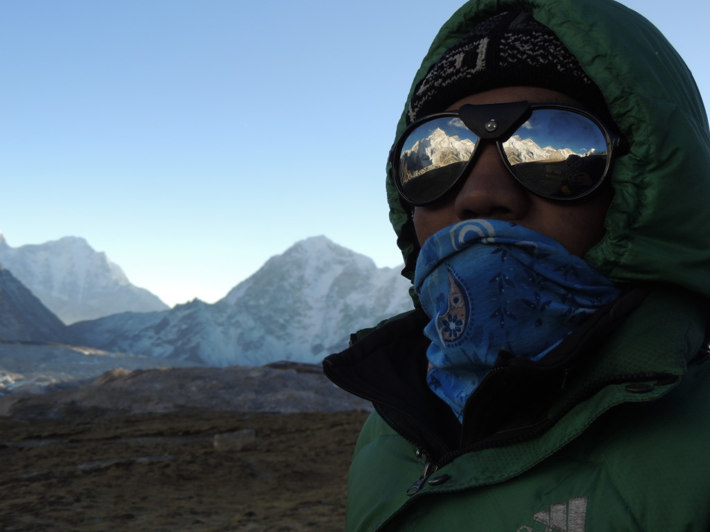 Photo 7. Pradap Tamang, who has been with me as my cook/guide for every trek in Nepal, with Everest reflected in his sunglasses. (Photo credit – H. Buckingham)
