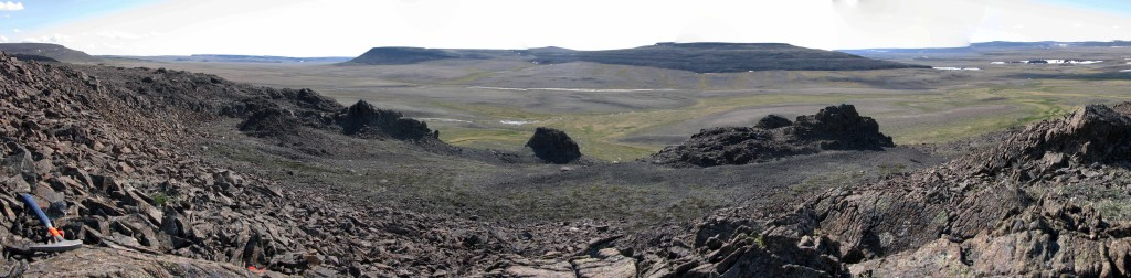 View of three volcanic vent necks preserved as erosional outliers among the adjacent flows and surrounded by deposits of loose scoria.