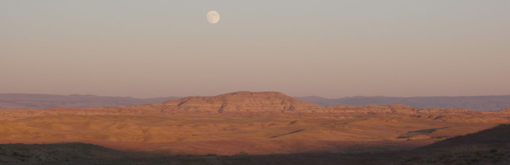 View from camp: moon rises over butte.
