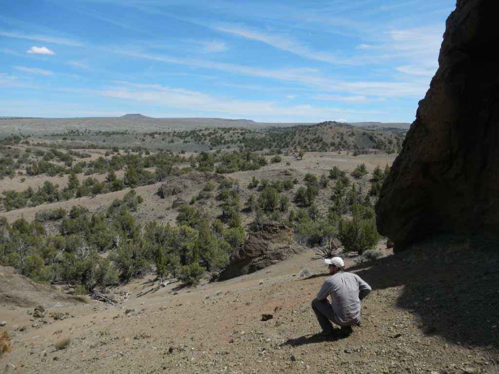 Matthew Nikitczuk pondering Oregonian geology from within the Black Hills. A volcano with a flat lava cap top is visible in the distance. Photo by Nevena Novakovic.