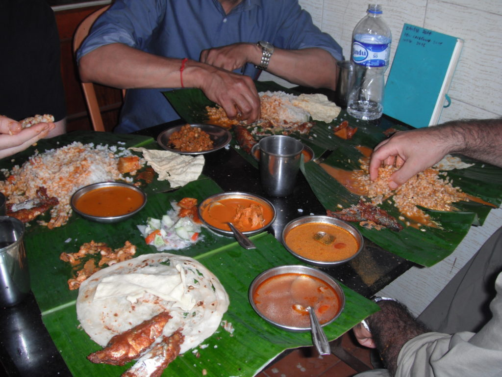 A typical serving of Indian food consisting of several curries, a tonne of rice, naan and fish – all served on a banana leaf.