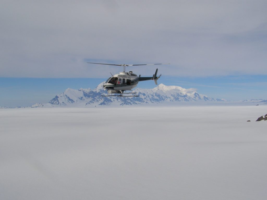Helicopter flying above Seward Icefield in front of Mount St. Elias in the southwest.