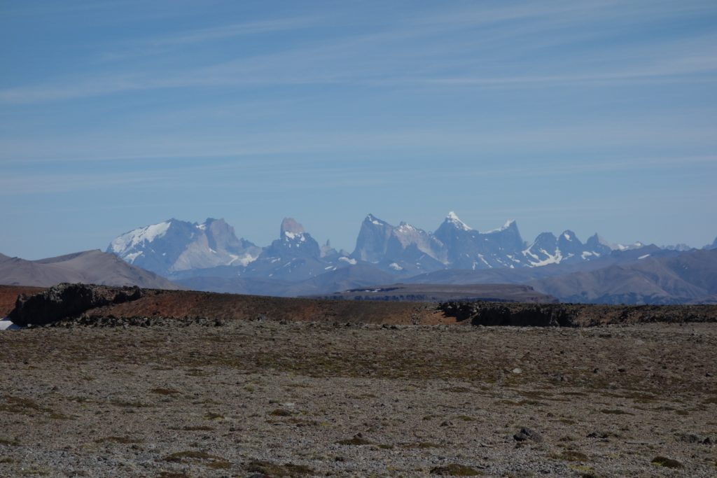 The peaks of Torres del Paine (background) seen from atop a basalt plateau (foreground). The Torres del Paine preserve an ancient magma chamber spectacularly exposed in 3-D. Even 150 km away, we could distinguish the intrusive magmatic rocks (pale colours) and the sedimentary rocks they were intruded into (dark colours).